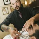 Hispanic barber shaving man's face